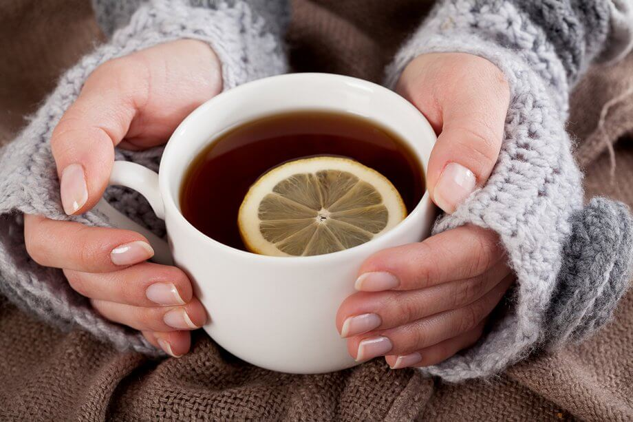 woman's hands with handwarmers on them holding a cup of tea with a slice of lemon