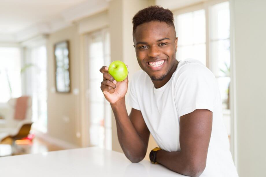 Young man with short dark hair is holding a green apple and smiling while in a kitchen.