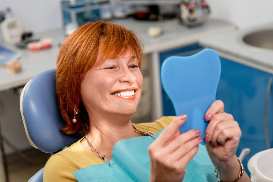 Senior Woman Admiring New Dental Implants