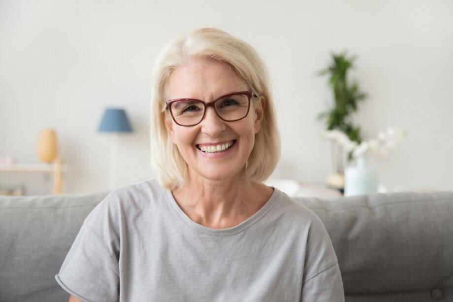 older blonde woman wearing red glasses, smiling